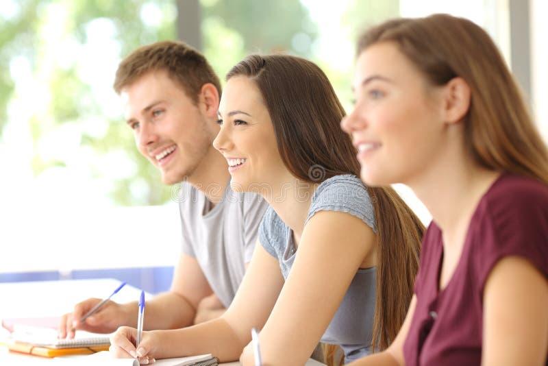 Drie studenten die in een klaslokaal luisteren stock fotografie