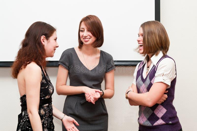 Drie studenten die in klaslokaal spreken royalty-vrije stock afbeeldingen