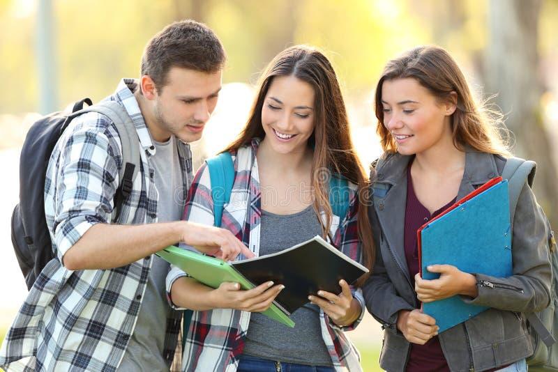 Drie studenten die lezingsnotitieboekje leren stock afbeelding