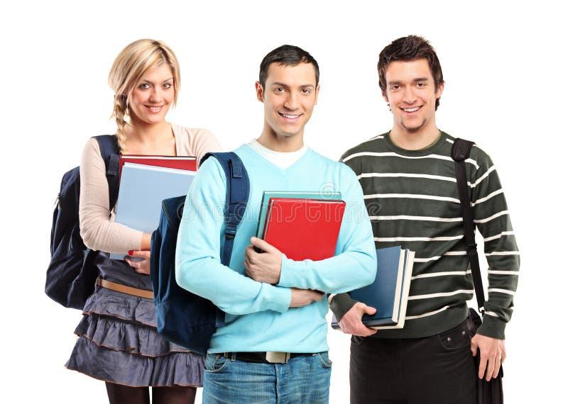 Drie studenten die met boeken stellen stock foto