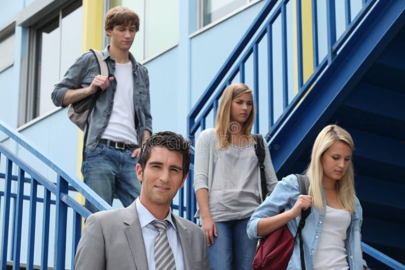 Drie studenten die onderaan treden lopen stock foto