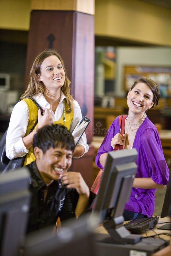 Drie studenten die uit in bibliotheek hangen stock foto