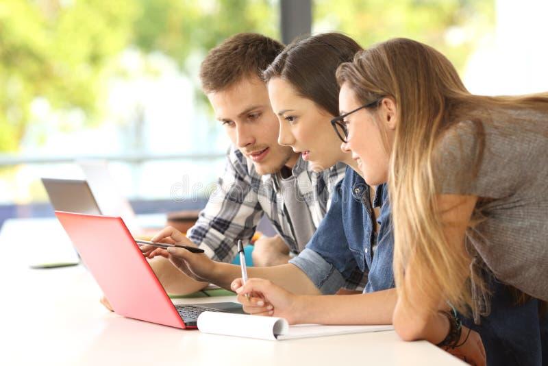 Drie studenten online bestuderen samen stock afbeeldingen