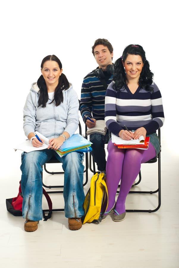 Drie studenten op stoelen stock foto's