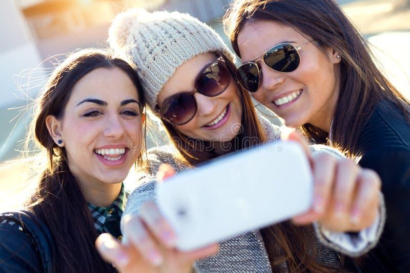 Drie studentenmeisjes die mobiele telefoon in de campus met behulp van stock foto's