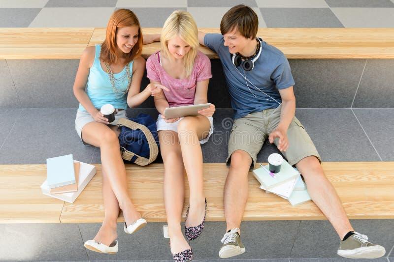 Drie studentvrienden met tablet en boek royalty-vrije stock foto