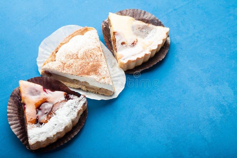 Drie stukken eigengemaakte pastei met fruit of bessen op een blauwe achtergrond royalty-vrije stock foto