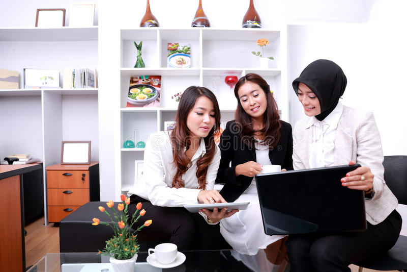 Drie succesvolle onderneemsters die bij bureauwoonkamer samenkomen stock afbeeldingen
