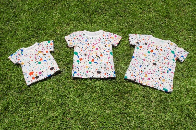 Drie T-shirts die op groen gras liggen De zomerkamp voor conceptuele kinderen, Grote familieachtergrond Behandeling van royalty-vrije stock afbeeldingen