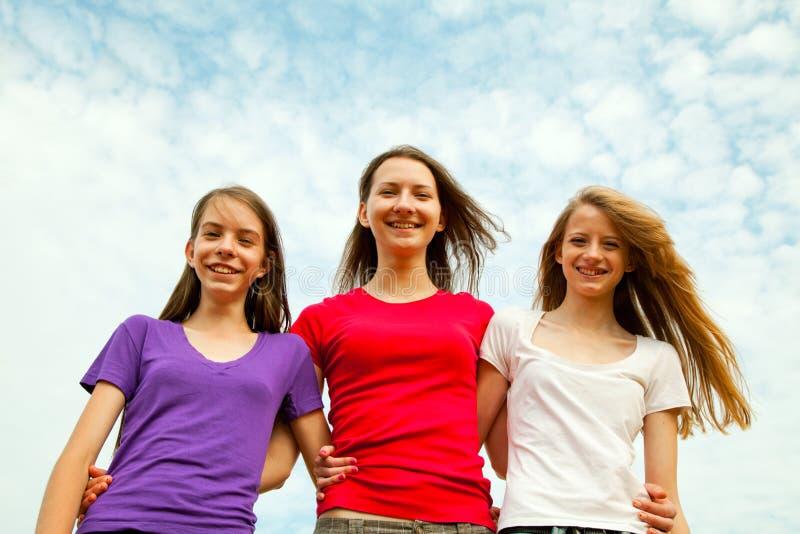 Drie tiener vrolijke meisjes stock afbeelding