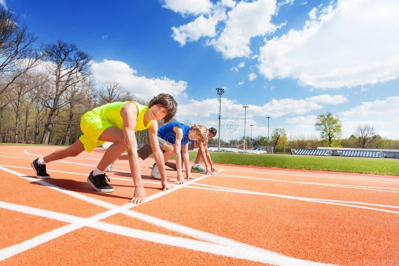 Drie tieneratleten stelden klaar te rennen op stock foto