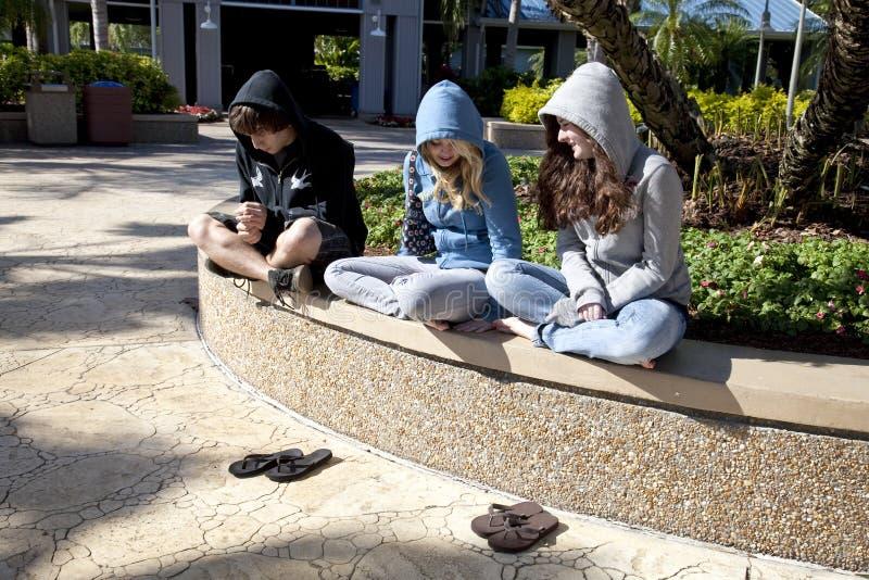 Drie Tienerjaren die samen zitten royalty-vrije stock afbeelding
