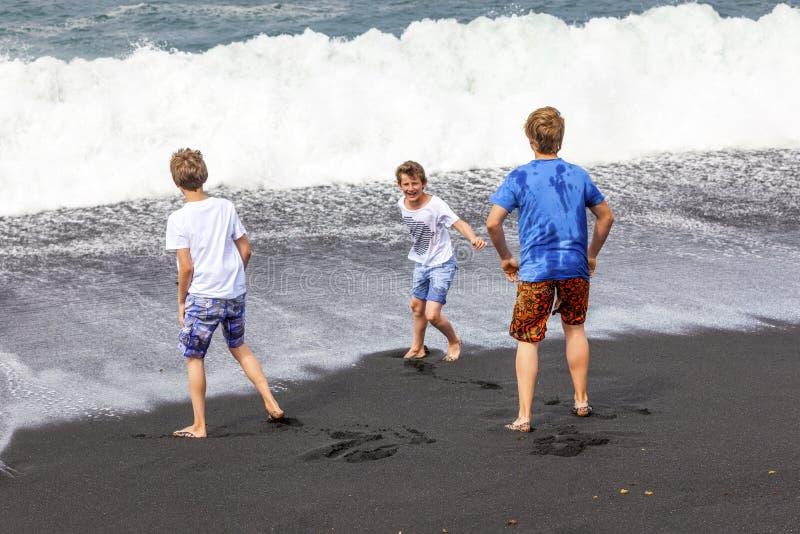 Drie tienerjongens hebben pret bij een zwart vulkanisch strand stock fotografie