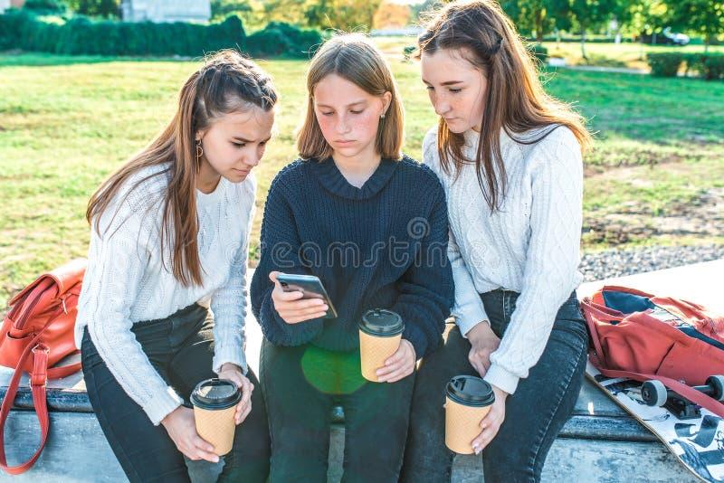 Drie tienermeisjes van 12-15 jaar oud, kijk op smartphone, video vaak internettoepassing, zomerherfststad stock fotografie