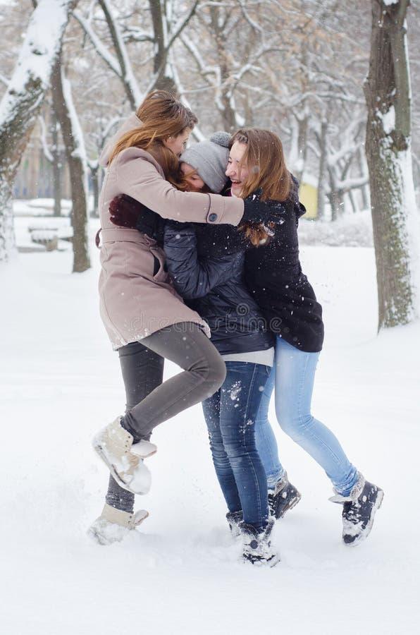 Drie tieners die in de sneeuw spelen stock afbeelding