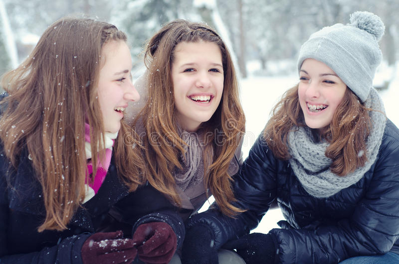 Drie tieners die pret in de sneeuw hebben stock foto's