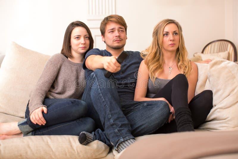 Drie tienerstudenten die op televisie letten stock foto's