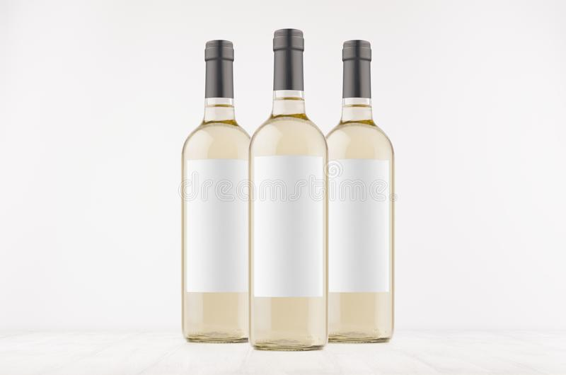 Drie transparante wijnflessen met lege witte etiketten op witte houten raad, bespotten omhoog stock afbeelding