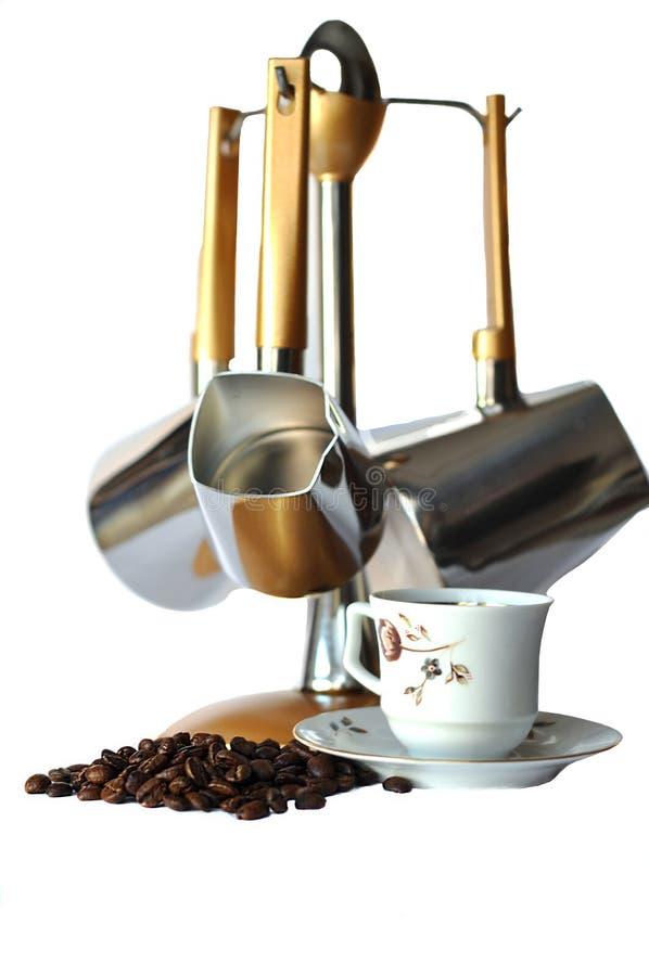 Drie Turken voor het koken van koffie op een metaal bevinden zich Een kop koffie en koffiebonen stock foto's