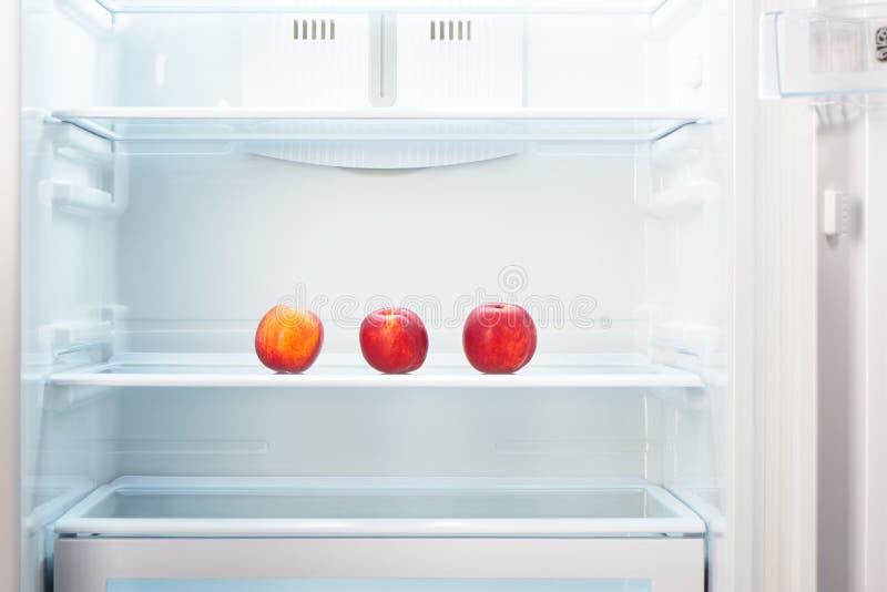 Drie twee-gekleurde oranje en rode perziken op plank van open lege ijskast stock foto's