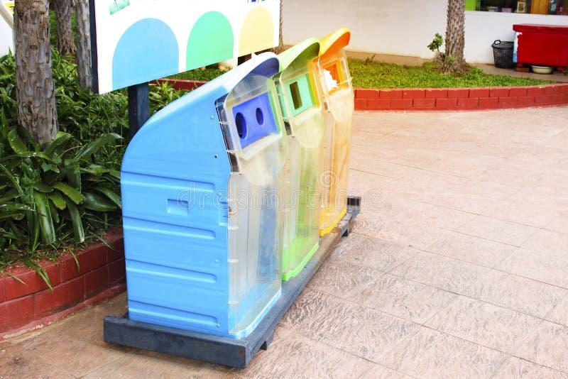 Drie types van vuilnisbakken, blauw, groen en oranje in het park royalty-vrije stock afbeelding