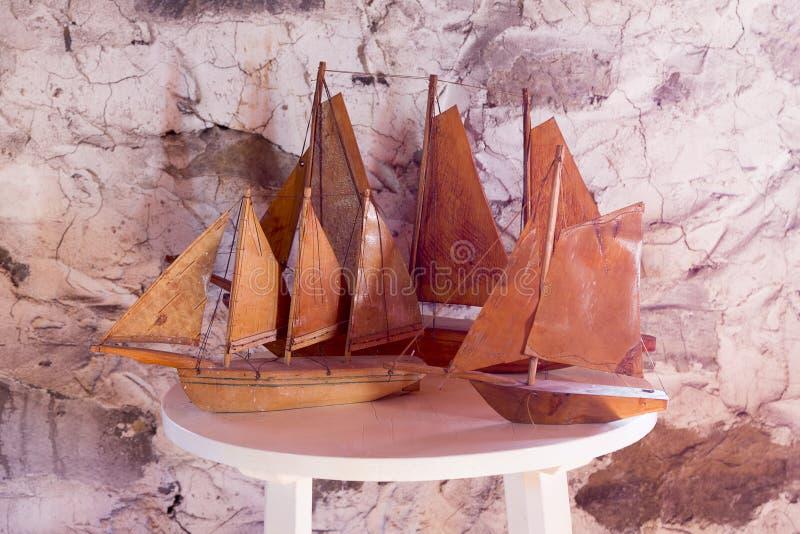 Drie uitstekende met de hand gemaakte houten zeilbootreplica's op witte rondetafel stock illustratie