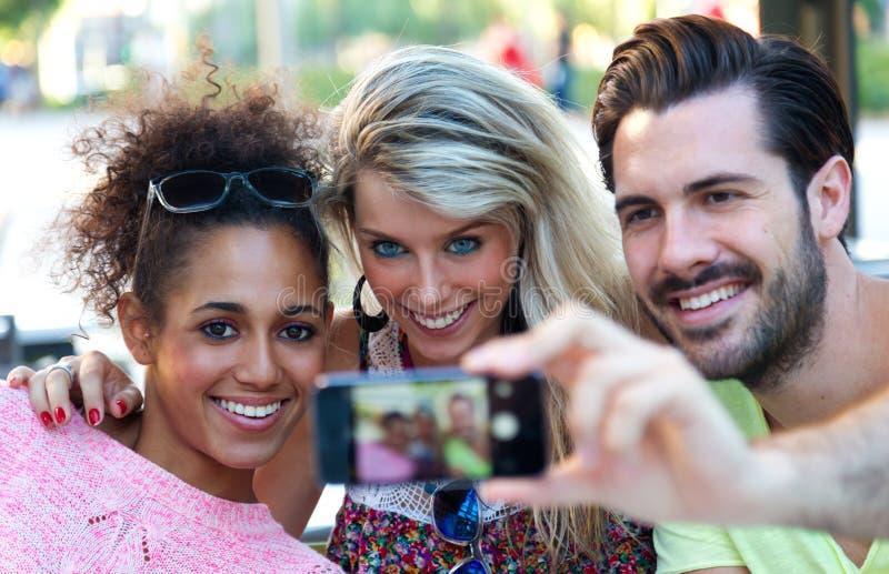 Drie universitaire studenten die een selfie in de straat nemen stock afbeeldingen