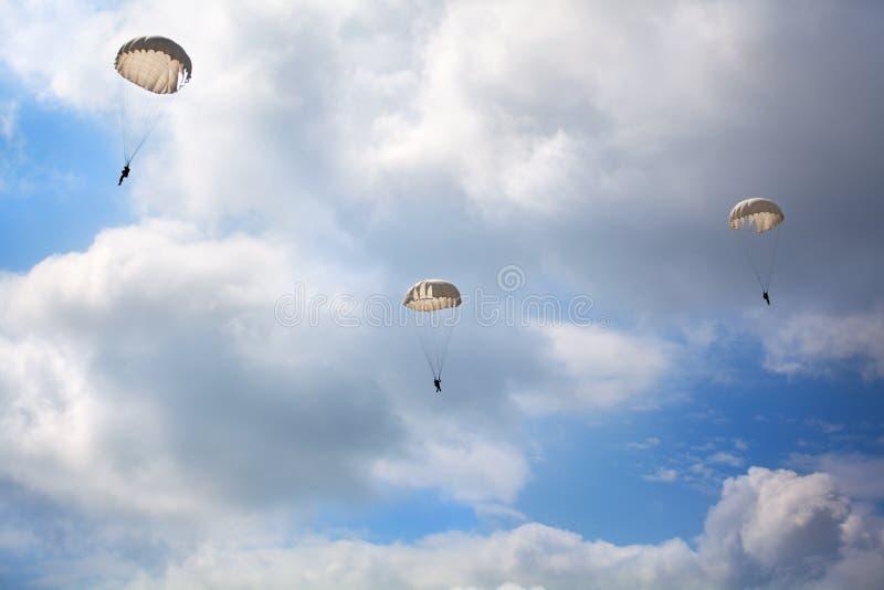 Drie valschermjagers springen met valschermen op de blauwe hemel met witte wolkenachtergrond stock foto's
