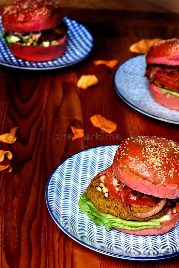 Drie vegetarische burgers in roze broodjes op blauwe platen stock afbeelding
