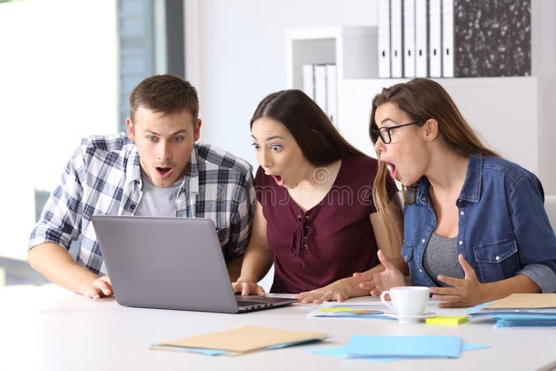 Drie verbaasde ondernemers online op kantoor stock afbeeldingen
