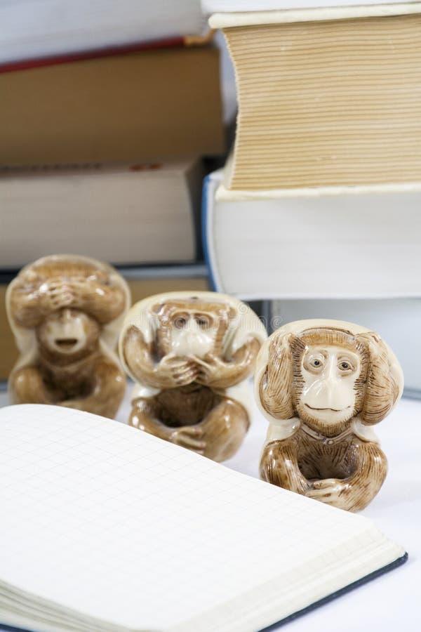Drie vermoeide apen met blocnote en vele dikke boeken royalty-vrije stock foto's