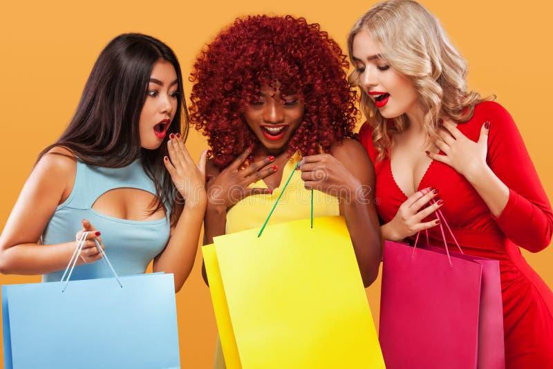 Drie verraste vrouwen na het winkelen Afro Amerikaanse, Aziatische en Kaukasische rassen Oranje achtergrond op zwarte vrijdag royalty-vrije stock afbeeldingen