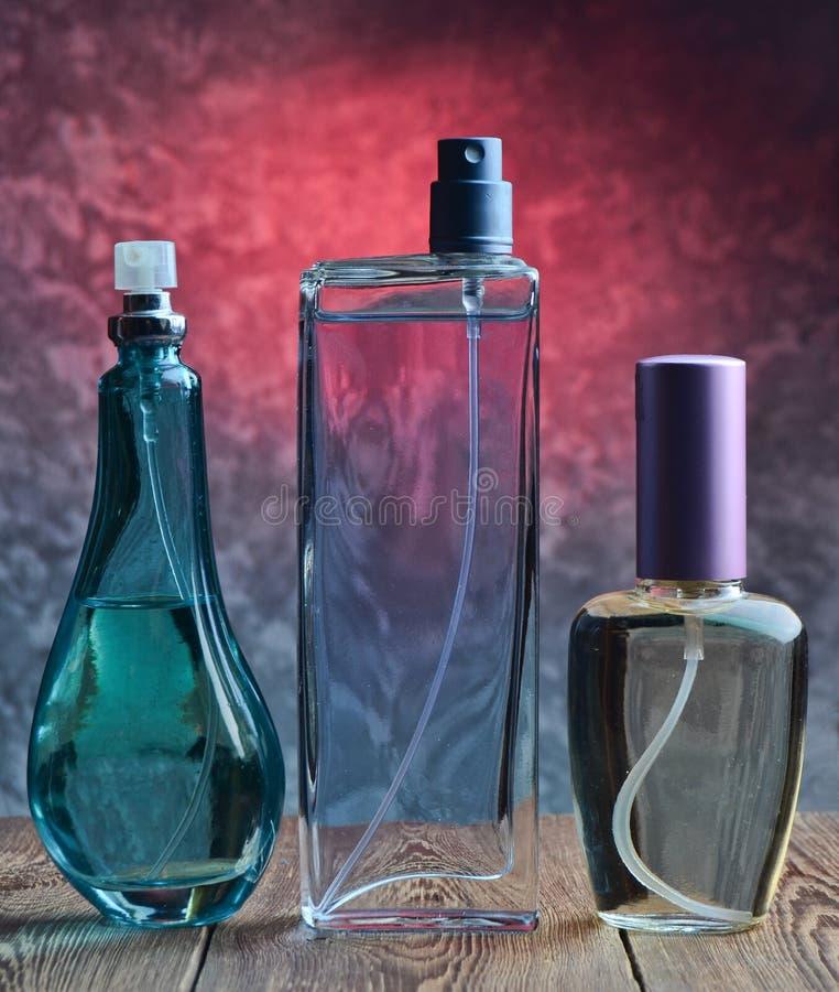 Drie verschillende flessen parfum op een houten plank tegen de achtergrond van een concrete muur stock foto's