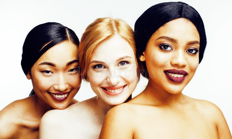 Drie verschillende natievrouw: Aziaat, Afrikaans-Amerikaan, Kaukasisch samen geïsoleerd bij het witte gelukkige glimlachen als ac royalty-vrije stock foto's