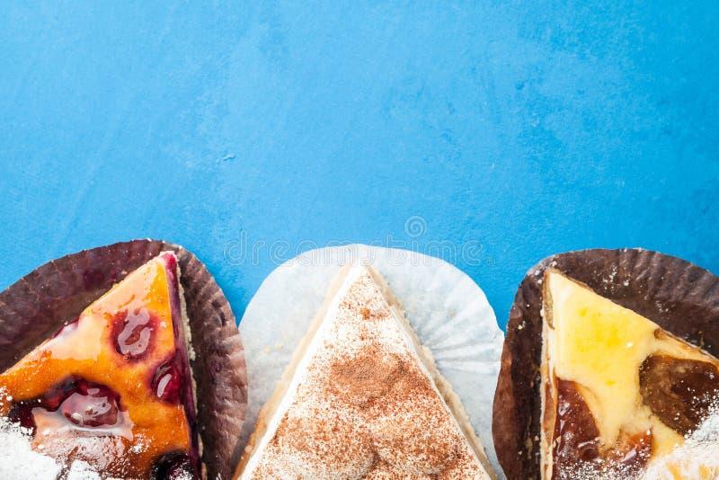 Drie verschillende stukken van pastei op een blauwe achtergrond met ruimte voor gelukwensen Concept een vakantie of een verjaarda stock foto's