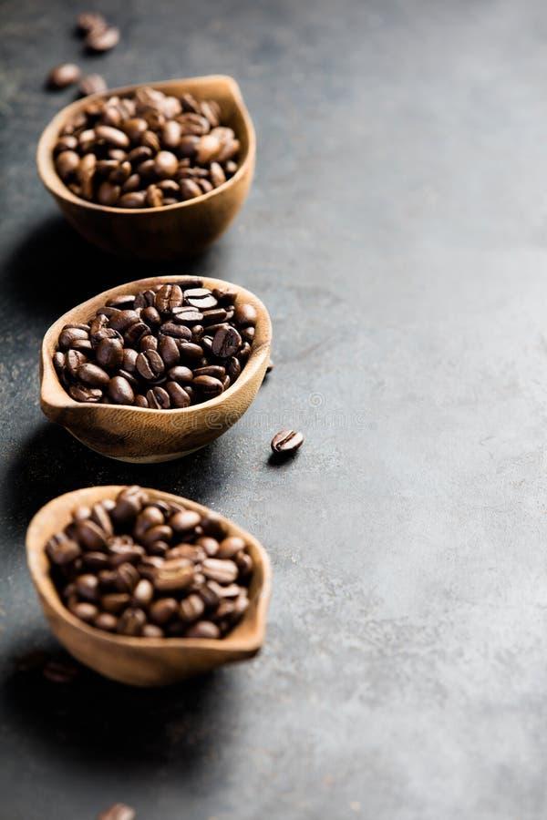 Drie verschillende verscheidenheden van koffiebonen op donkere uitstekende achtergrond stock afbeeldingen