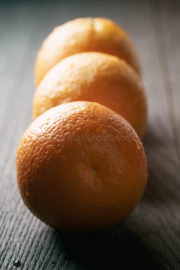 Drie verse rijpe sinaasappelen op eiken houten lijst stock foto's