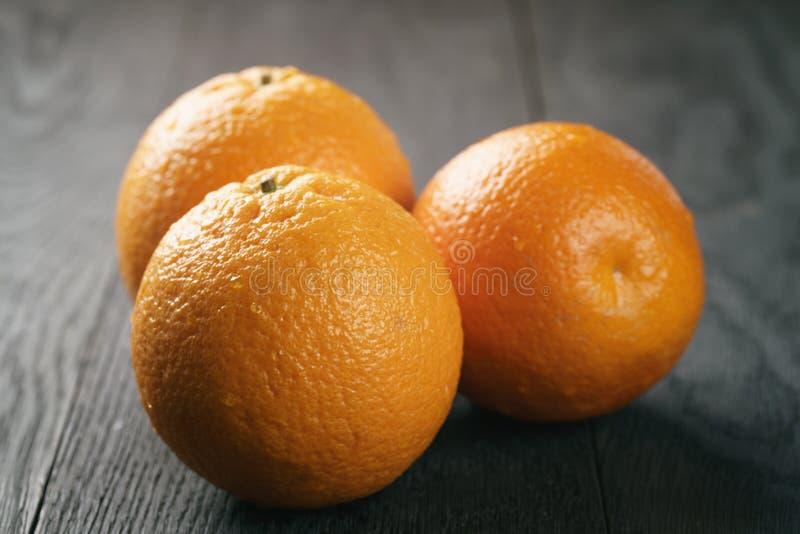 Drie verse rijpe sinaasappelen op eiken houten lijst royalty-vrije stock afbeelding