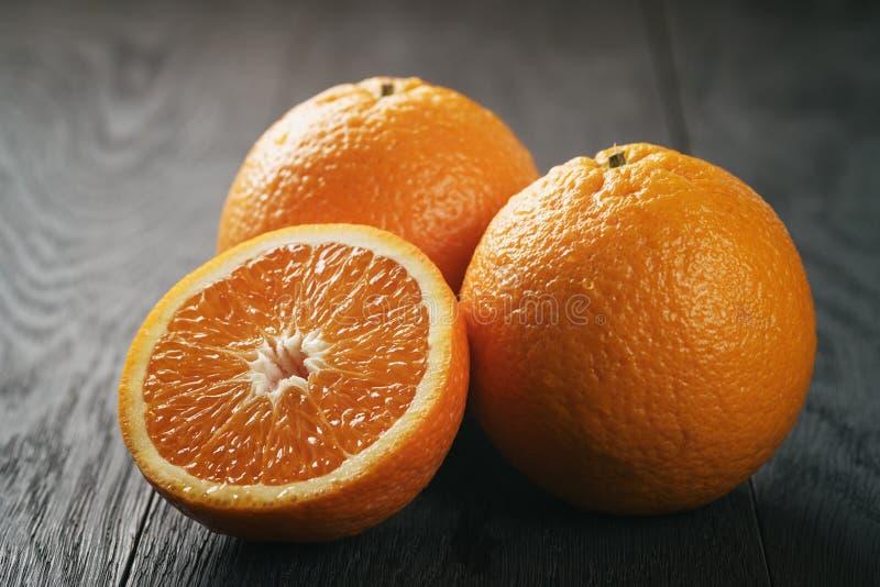 Drie verse rijpe sinaasappelen op eiken houten lijst stock afbeelding