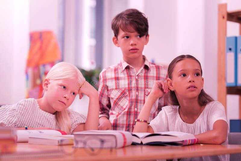 Drie verwarde leerlingen die aan hun leraar luisteren stock foto