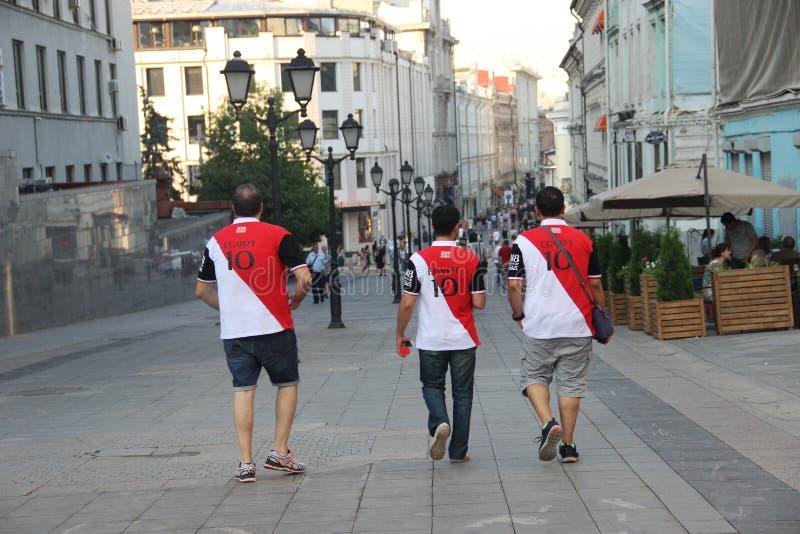 Drie voetbalventilators in t-shirts met de inschrijving Egypte en aantal tien royalty-vrije stock afbeelding