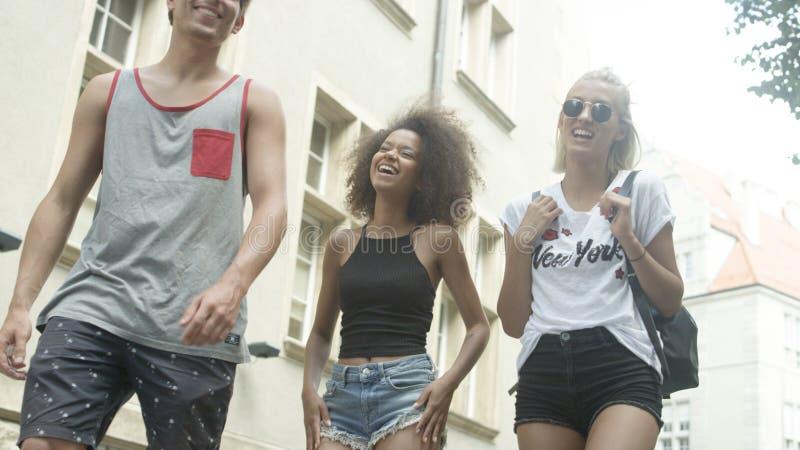 Drie vrienden die aan elkaar spreken aangezien zij die samen in een stad lopen royalty-vrije stock fotografie