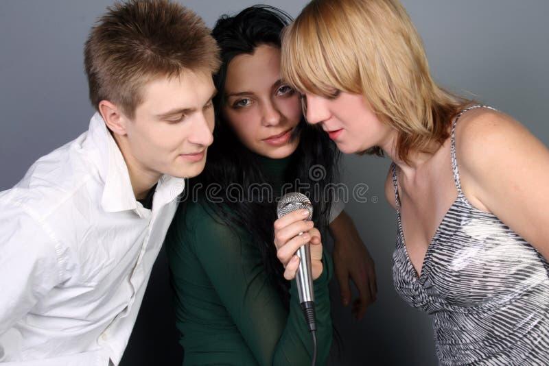 Drie vrienden die een lied zingen royalty-vrije stock afbeelding