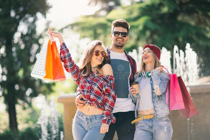 Drie vrienden die gekleurde zakken in hand houden stock fotografie