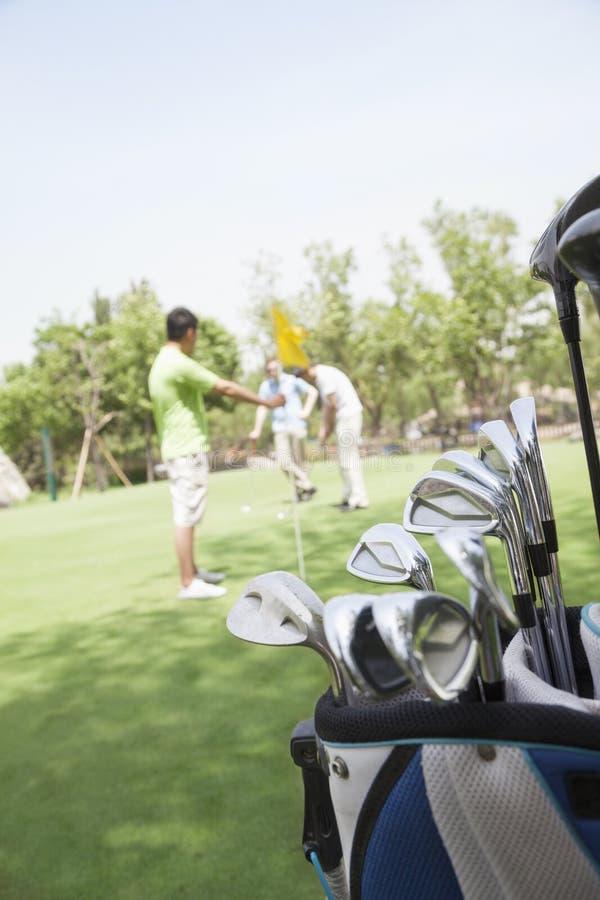 Drie vrienden die golf op de golfcursus, nadruk op de theebus spelen stock foto's