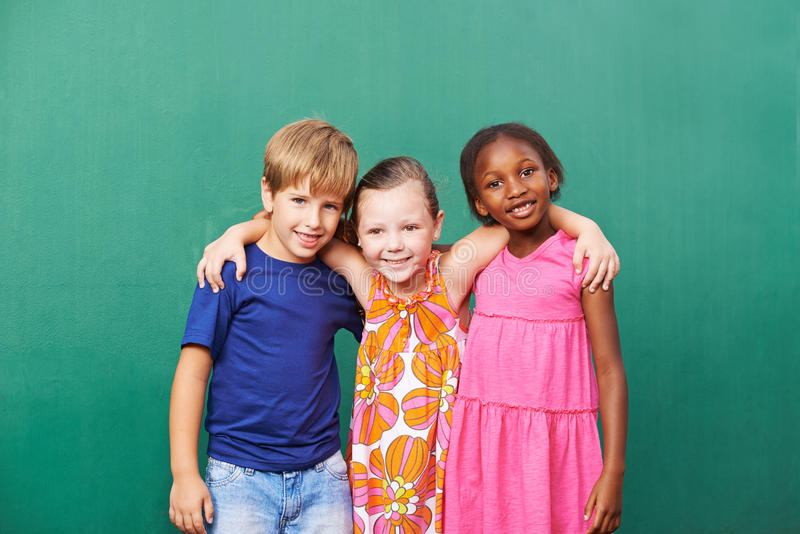 Drie vrienden die in kleuterschool omhelzen stock foto's