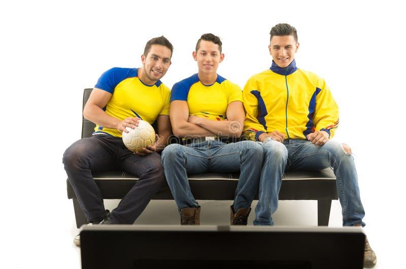 Drie vrienden die op bank zitten die gele sportenoverhemden dragen die op televisie met enthousiasme, witte achtergrond, schot le stock foto