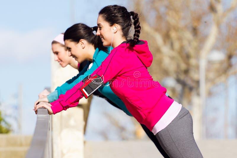 Drie vrienden die opdrukoefeningen doen stock fotografie