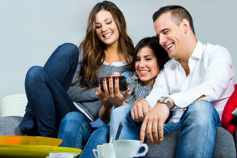 Drie vrienden die pret met een mobiele telefoon hebben stock foto's