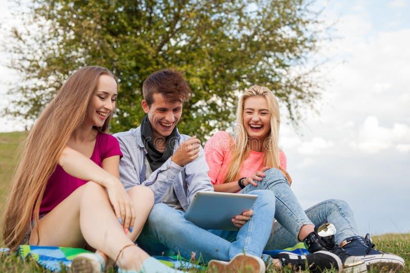 Drie vrienden die spel op tabletpc spelen Zij die opnieuw winnen royalty-vrije stock foto's